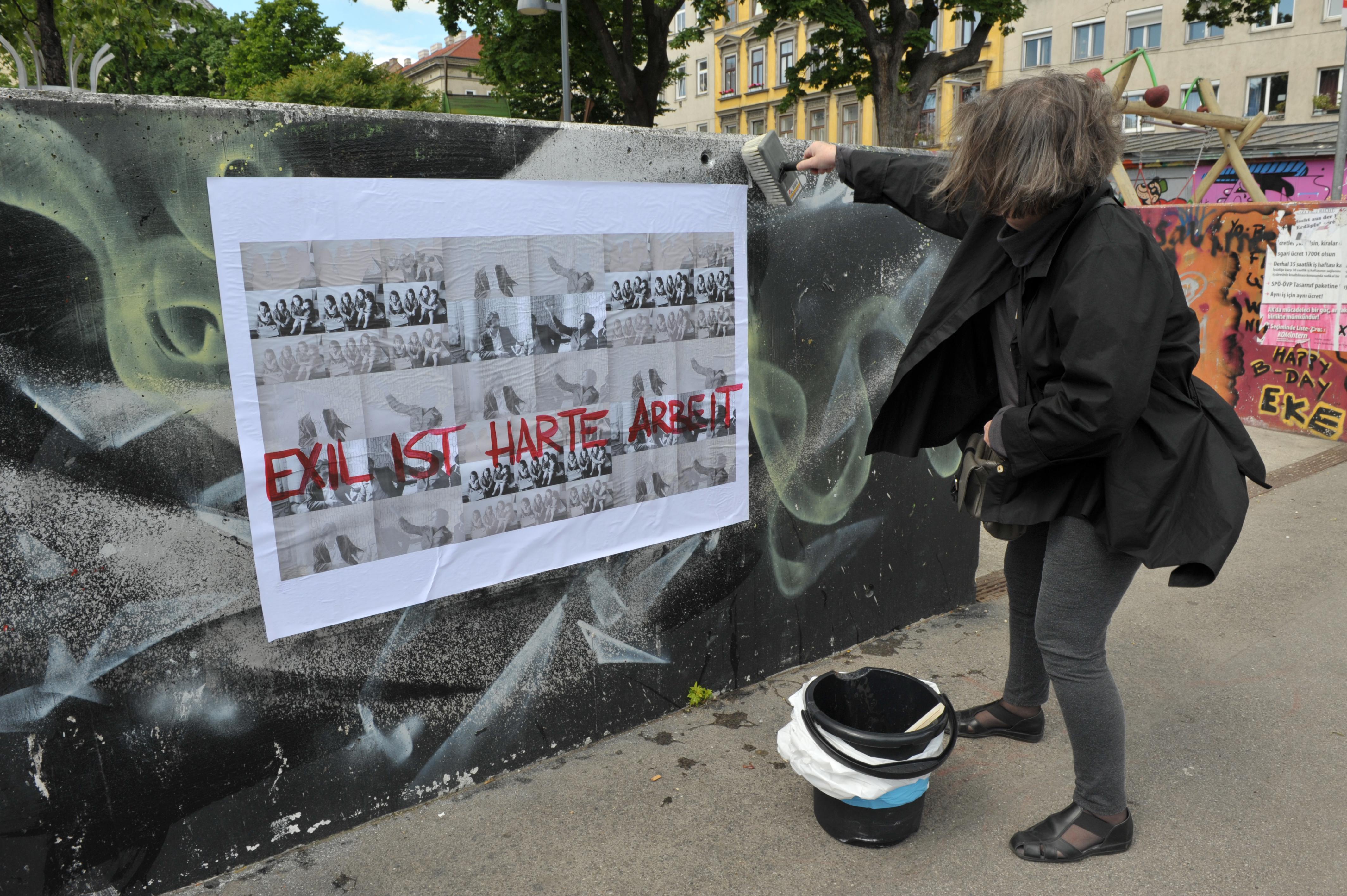 © Nil Yalter beim Plakatieren im öffentlichen Raum, EXIL IST HARTE ARBEIT, 2014, Plakataktion in Wien